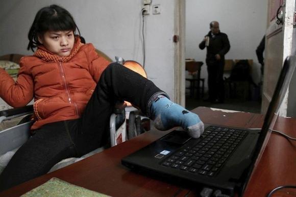 Pechino: ragazza paralizzata dalla nascita scrive un libro con il piede sinistro. Scrive 30 parole al minuto