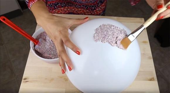 Gonfia un palloncino e lo ricopre di glitter. Ecco cosa crea