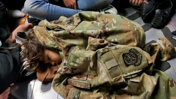 Bimba dorme in un cargo avvolta da una giacca dell'Air Force: scatto simbolo del dramma afghano