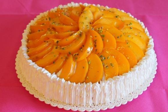 Torta con crema Chantilly, pesche e granella di pistacchio