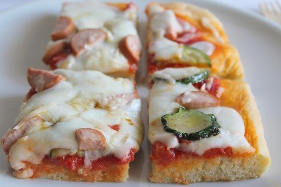 Pizza al taglio con zucchine, wurstel e scaglie di Parmigiano Reggiano