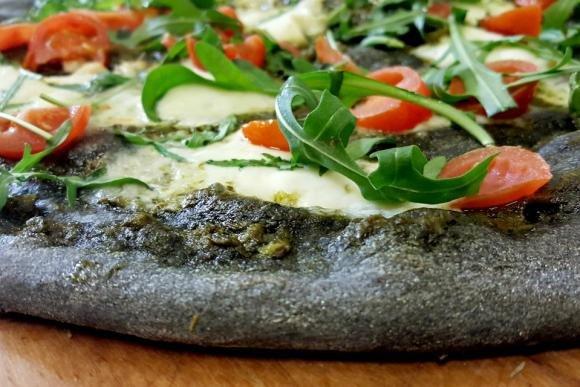 Pizza al carbone vegetale con crema di rucola e stracchino