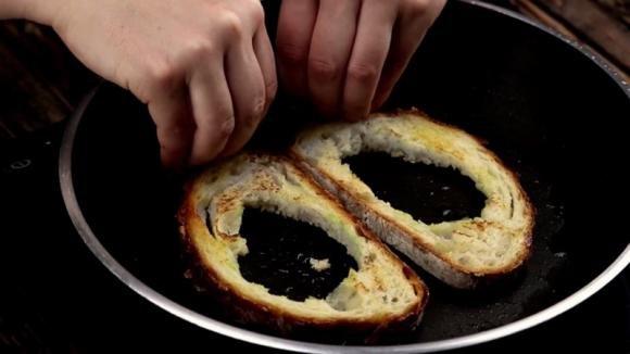 Buca due fette di pane e le abbrustolisce in padella. Poi le riempie e realizza un piatto gustoso e veloce