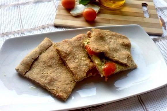Schiacciata integrale al pesto con pomodorini e mozzarella di bufala