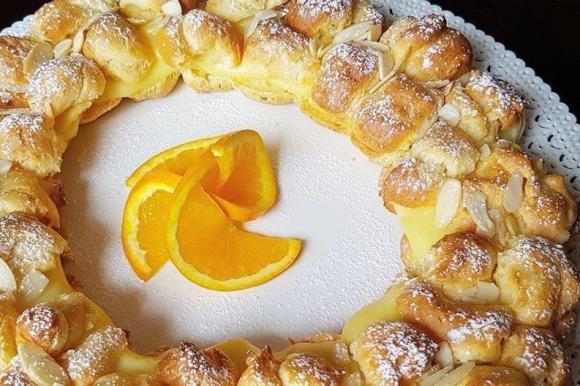 Corona di bignè con crema all'arancia e scaglie di mandorle