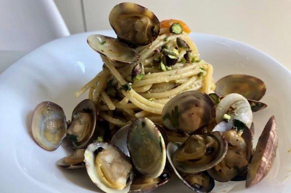 Spaghetti con vongole veraci, pomodorini gialli e pistacchi