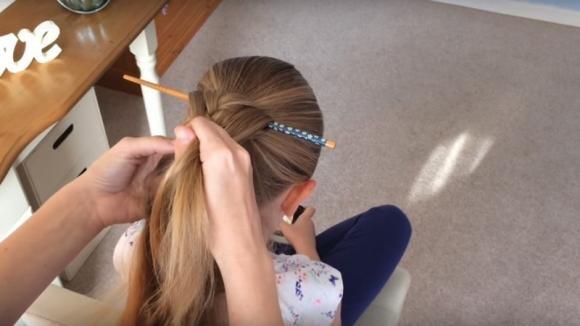Mette un bastoncino fra i capelli e fa una treccia. Quando lo toglie ottiene un'acconciatura strepitosa