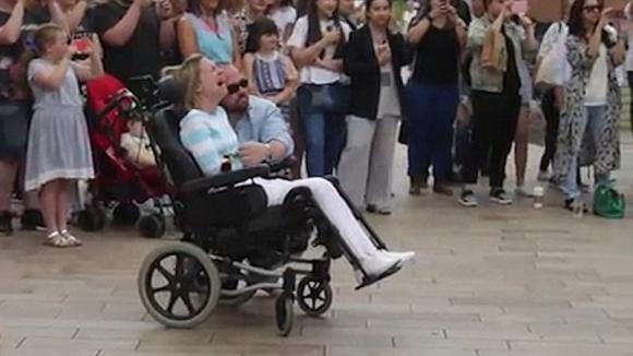 Un estraneo regala una rosa alla donna sulla sedia a rotelle. Poi suo marito le indica le scale e lei scoppia in lacrime