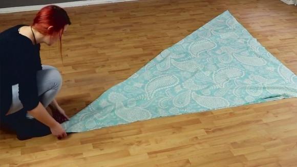 Stende una tenda sul pavimento ed inizia a piegarla. Ottiene così il vestito più semplice del mondo