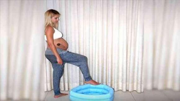 Una donna incinta entra in una piscina gonfiabile. Guardate cosa succede ai suoi pantaloni quando esce fuori!