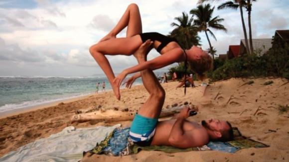 Fanno yoga sulla spiaggia. Lei non immagina la sorpresa che l'attende a testa in giù!