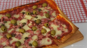 Pizza di sfoglia con prosciutto, olive e capperi